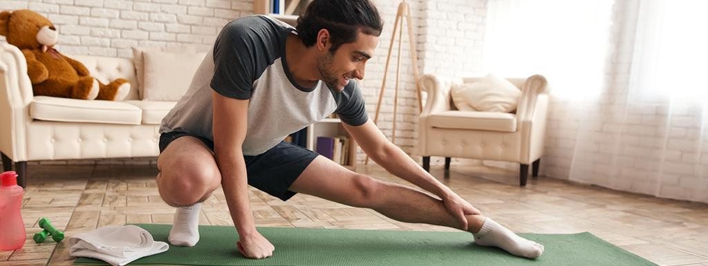 Man exercising gently in his front room
