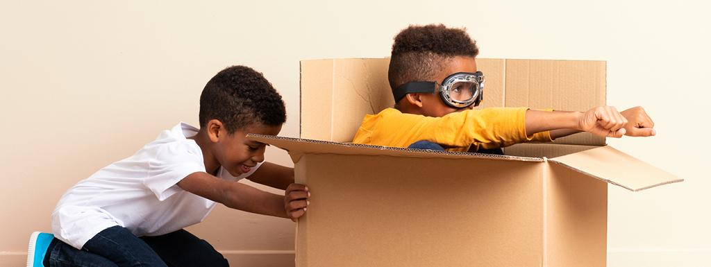 Two kids playing, one hiding in a cardboard box