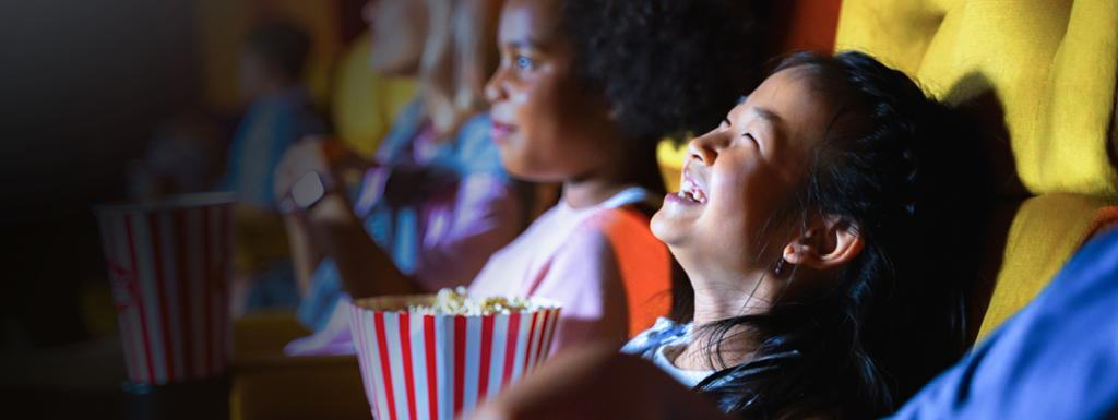 Kids watching film in a cinema whilst eating popcorn
